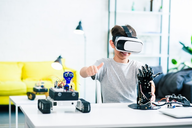 Enthusiastic smart little boy sitting at the table while experimenting with humanoid robotic hand and vr glasses