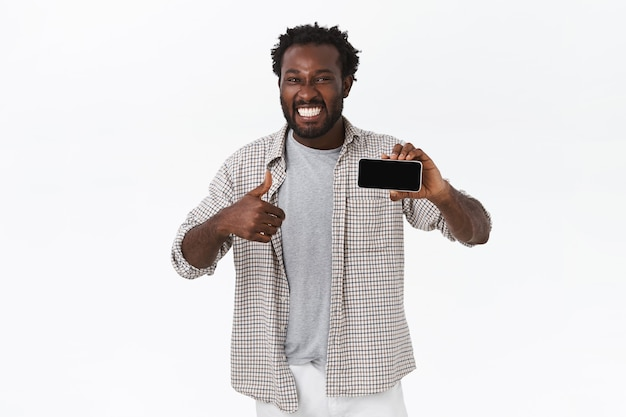 Enthusiastic smiling happy african american guy amazed with awesome new app