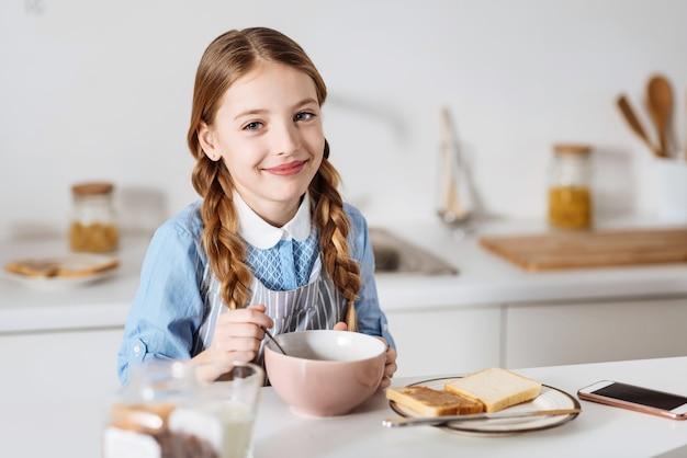 열정적 인 시작. 부엌의 테이블에 앉아있는 동안 시리얼, 샌드위치, 우유로 구성된 그녀의 아침 식사를 즐기는 낙관적 귀여운 달콤한 아이