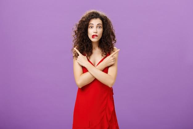 Entusiasta insicuro emotiva donna elegante in elegante abito da sera rosso mordere il labbro cercando eccitato che punta in direzioni diverse a sinistra ea destra essendo incerta e dubbiosa nel prendere una decisione.