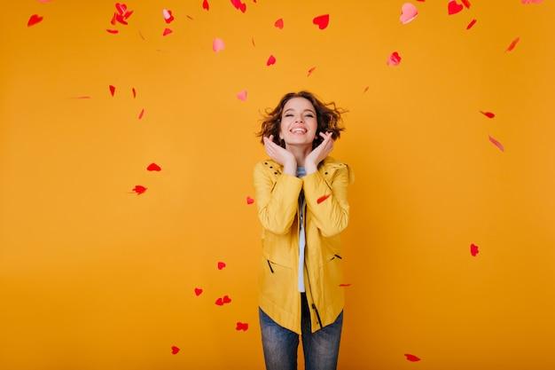 幸せな笑顔でポーズをとる流行のカジュアルな服を着た熱狂的な白人女性モデル。落ちた心の下に立っている黄色いジャケットの素晴らしい女の子。
