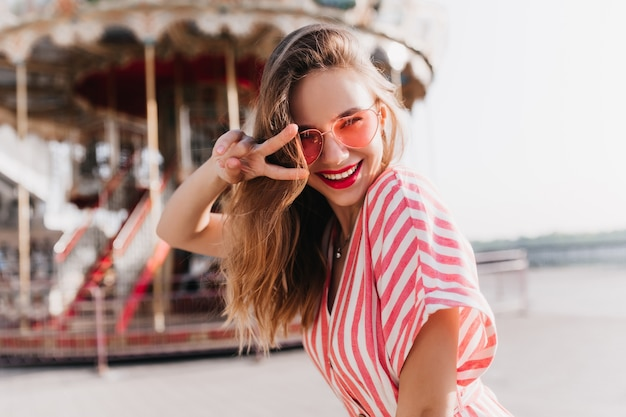 Enthusiastic white girl funny dancing near carousel. happy young woman wears pink striped attire posing in amusement park with smile.