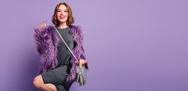 スタジオで踊るファッショナブルな紫色のジャケットの熱狂的な白人の女の子