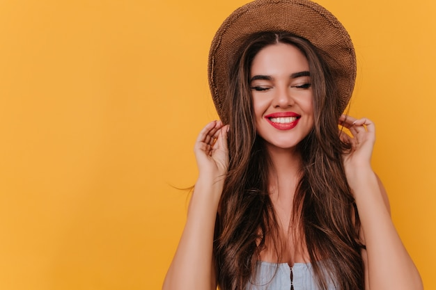 Entusiasta ragazza bianca con lunghi capelli castano scuro in posa con un sorriso carino