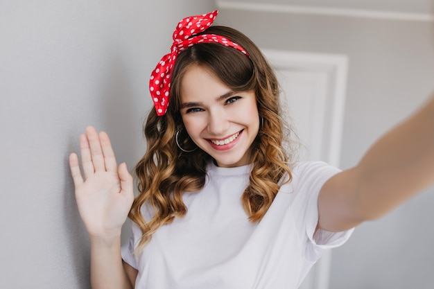 Enthusiastic white girl with wavy shiny hair taking picture of herself at home. indoor photo of happy female model with red ribbon making selfie.
