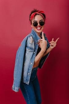 Donna bianca entusiasta in occhiali da sole alla moda e vestiti di jeans che ride mentre posa