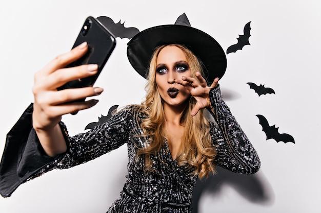 박쥐와 함께 셀카를 만드는 어두운 화장으로 열정적 인 마녀. 매력적인 여성 뱀파이어 흰 벽에 포즈입니다.