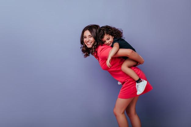紫色の壁に巻き毛の子供と遊ぶショートドレスの熱狂的な女性。笑っている若い女性と彼女の小さな娘の屋内写真。