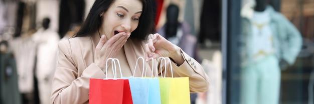 熱狂的な女性がモールで買い物袋を調べます