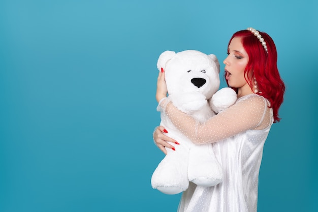 Enthusiastic woman in a white dress with red hair and an open mouth embraces a white teddy bear
