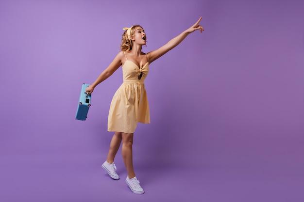 Donna entusiasta con valigia blu in mano che punta il dito a qualcosa. ritratto a figura intera di ragazza curiosa divertente in abito giallo.