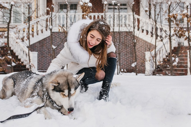 ハスキーの子犬を見て、笑顔の明るい茶色の髪の熱狂的な女性。雪の上の犬と一緒にポーズ至福の若い女性の屋外のポートレート。