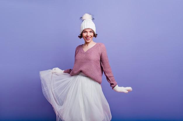 La donna entusiasta in guanti di lana gioca con la gonna isolata sulla parete viola. ragazza felice in cappello e guanti bianchi.