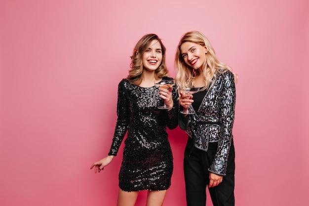 パーティーの熱狂的な女性は何かを祝う服装をしています。ワインを楽しんでいる笑顔の楽しい姉妹の屋内写真。