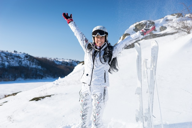 Enthusiastic young adult skier in long hair and white snowsuit throwing snow above her head with upright skis on hill behind her