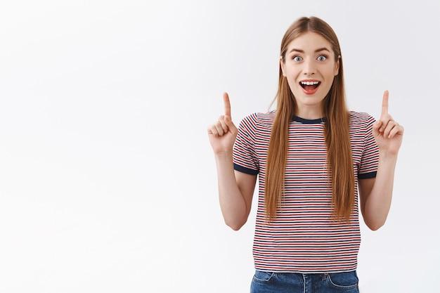 Восторженная молодая кавказская женщина в полосатой футболке с открытым ртом, задыхаясь, восхищенно смотрит в камеру, заинтригованная и удивленная, указывая вверх, проверяя удивительное промо, стоя на белой стене ошеломленно