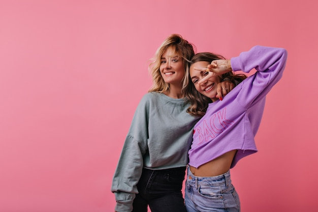 トレンディなシャツを着た熱狂的な若い女性がピンクに浮かんでいます。ピースサインでポーズをとる至福の親友。