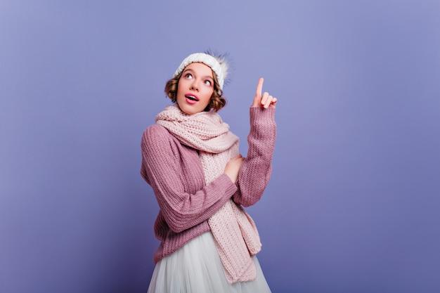 長いスカーフでポーズをとる短い髪の熱狂的な若い女性。紫色の壁に隔離された冬の服装で魅力的なヨーロッパの女性の屋内写真。