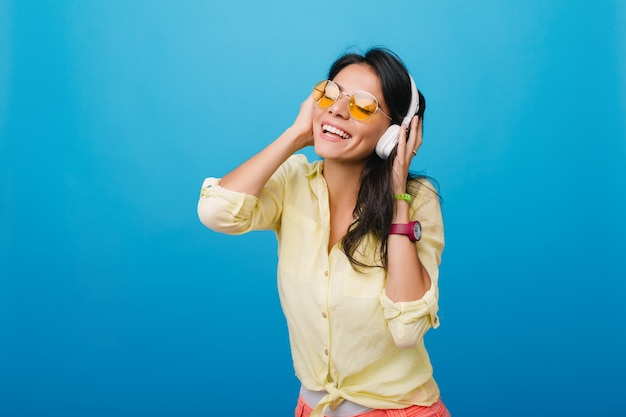 歌を楽しみながらヘッドフォンに触れるスタイリッシュな黄色のシャツとピンクのブレスレットの熱狂的な若い女性。光沢のある濃い茶色の髪のポーズで至福のヒスパニック系の女の子の屋内写真。