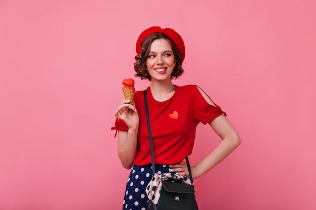 아이스크림을 먹고 최신 유행의 옷에 열정적 인 젊은 여자. 디저트와 함께 웃는 평온한 아가씨의 실내 사진.
