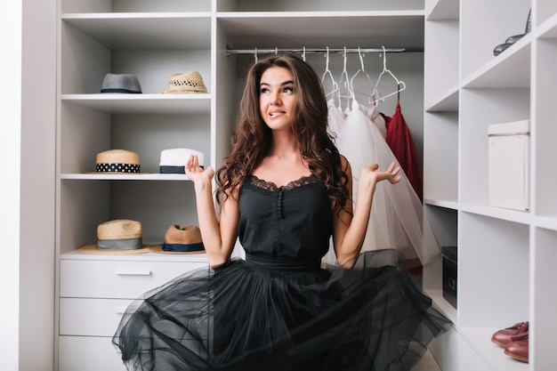 La giovane donna entusiasta che sta nello spogliatoio, nel guardaroba e nel pensiero, ha sguardo contemplativo. il suo bellissimo vestito nero aleggia nell'aria. ha lunghi capelli castani ricci.