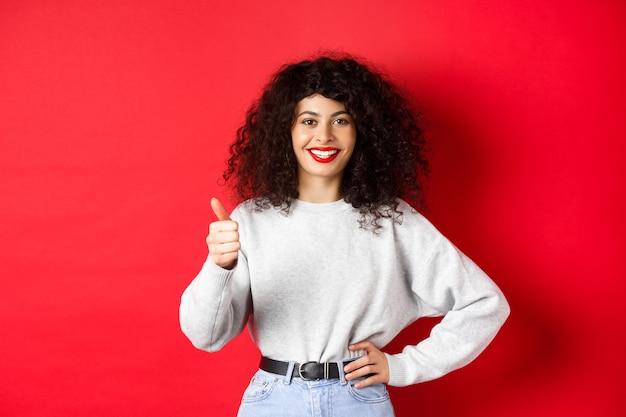 巻き毛、赤い唇、親指を立てて笑顔を見せて、承認を得て、良い製品を賞賛し、赤い背景に立っている熱狂的な若い女性