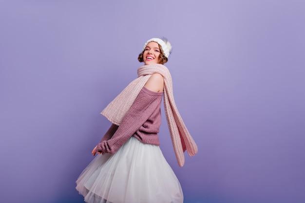 暖かい服を着てポーズをとって喜んで笑顔で熱狂的な若い女性。紫色の壁に浮かんでいる帽子とスカーフのインスピレーションを得た白人の女の子の屋内の肖像画。