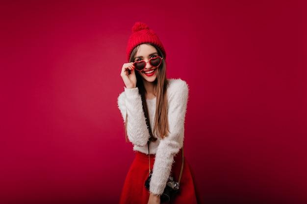Giovane donna entusiasta con vestito alla moda che tocca i suoi occhiali e che sorride