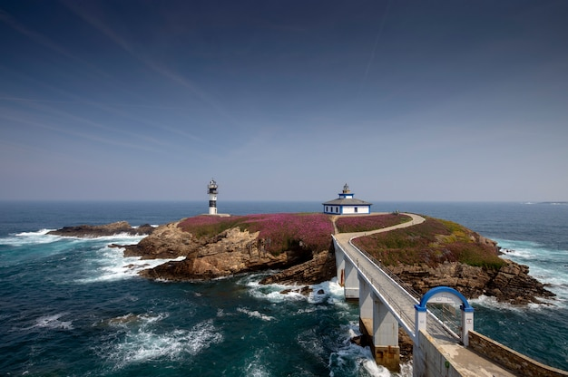 Entrance bridge to the lighthouse on pancha island on a sunny day and blooming vegetation. ribadeo lugo