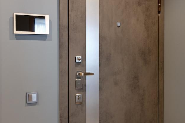 현대 아파트 복도의 입구 문, 벽에 비디오 인터콤 장치. 중성 톤.