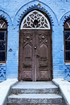Entrance door in an old abandoned house with lock