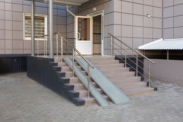 Entrance group with a ramp of a multistorey residential building stairs with metal ramp apartment building entrance