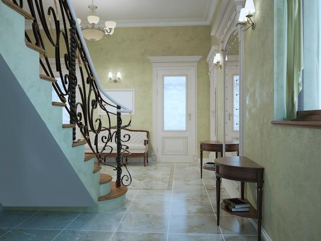 テクスチャード加工の漆喰の明るいオリーブ色の壁とマホガニーと大理石のタイルの床の家具を備えた階段のあるエントランスホールのクラシックなスタイル。