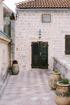 The entrance to the house is closed metal door with a grate through the yard with large pots