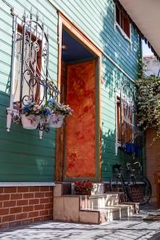 터키 이스탄불의 창문, 계단 및 주차 된 자전거에 꽃이있는 주거용 건물 입구
