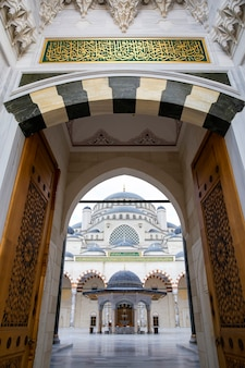 Вход во внутренний двор мечети камлика с людьми внутри, белый мрамор, стамбул, турция