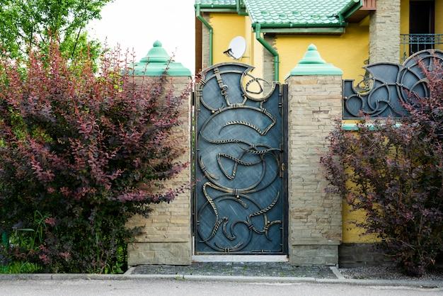 Въездные железные ворота с элементами ковки с каменным забором, украшающим дом