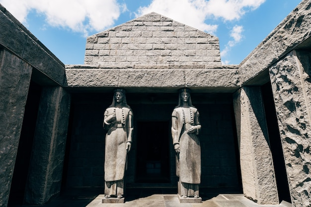 Entrance to the mausoleum of peter ii petrovic njegos with two tall statues, on top of mount lovcen