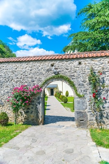 The entrance to the monastery of moraca, in montenegro, is decorated with flowers and plants