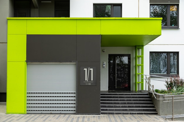 Entrance number one to new freshly painted block of flats with roller-shutter door