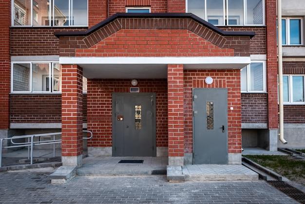 Подъезд жилого дома с металлической дверью с домофоном.