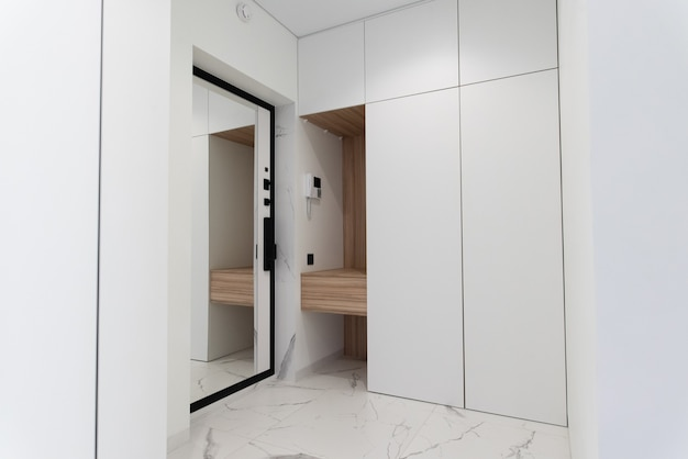 Entrance room in light colors with a natural wood shelf entrance mirror door marble tiles