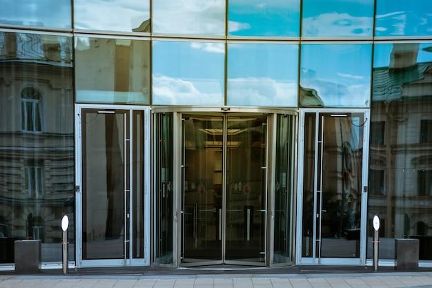 자동문이 있는 비즈니스 도시의 현대적인 사무실 건물 입구. 고층 빌딩은 현대적인 스타일로 설계되었습니다. 대도시의 비즈니스 지구에 건물의 아키텍처입니다. 저작권 공간