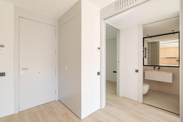白い壁と木製の床の入り口への眺めを備えたモダンなアパートのインテリアへの入り口...