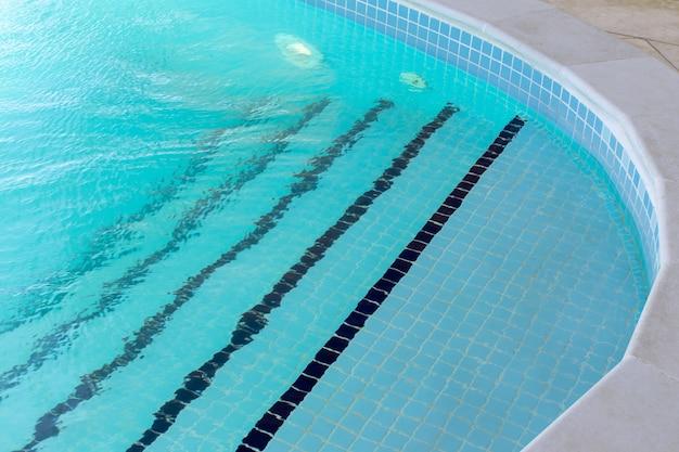 맑은 청록색 물이있는 수영장 입구, 가장자리를 따라 타일로 된 계단. 측면보기.