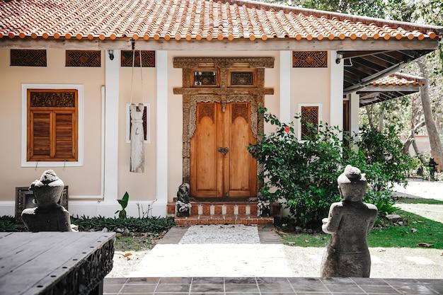 Вход в желтый дом. старая деревянная дверь с резными узорами. каменная дорожка, ведущая к запертой двери.
