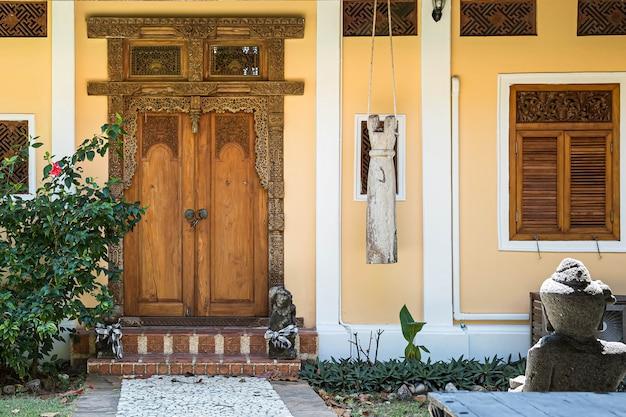 Вход в желтый дом с окном. старая деревянная дверь с резными узорами. каменная дорожка, ведущая к запертой двери.