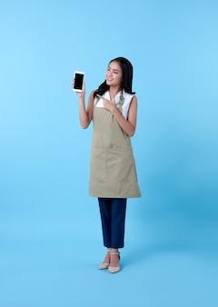 Donna asiatica dell'imprenditore che utilizza smartphone sull'azzurro.