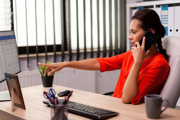 Entrepreneur businesswoman in professional call pointing at documents on computer screen. busy freelancer working using smartphone from office to talk with clients sitting at desk looking at document.