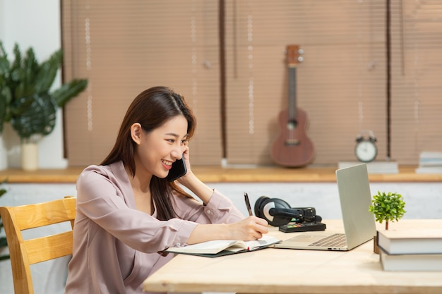 携帯電話を使用して起業家の実業家が同僚と話し、ラップトップで作業する